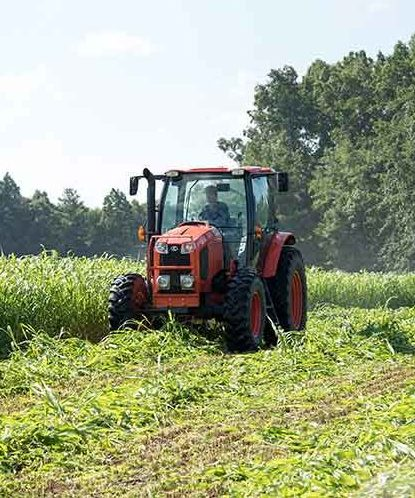 Okd red tractor on farm plowing field